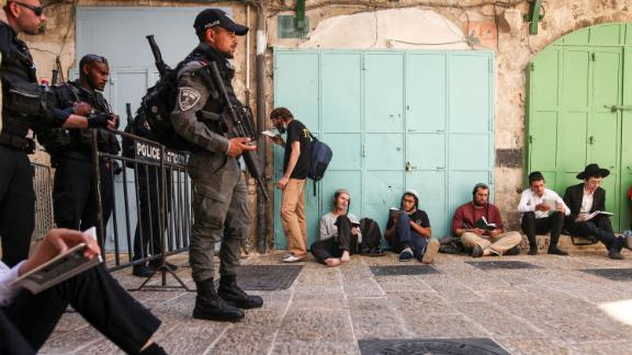 A group of Orthodox Jewish men pray outside one of the entrances to the Temple Mount/Haram al-Sharif, as Israeli security forces stand guard at a barrier, during the annual Tisha B'Av (Ninth of Av) fasting and memorial day, commemorating the destruction of ancient Jewish temples some 2000 years ago, on Sunday, July 18.