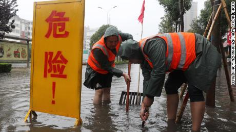 Workers drain water from a flooded area in Lanzhou, Henan, China on July 20.
