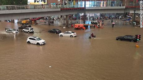 People stranded in flood waters along a street following heavy rains in Zhengzhou, China on July 20.