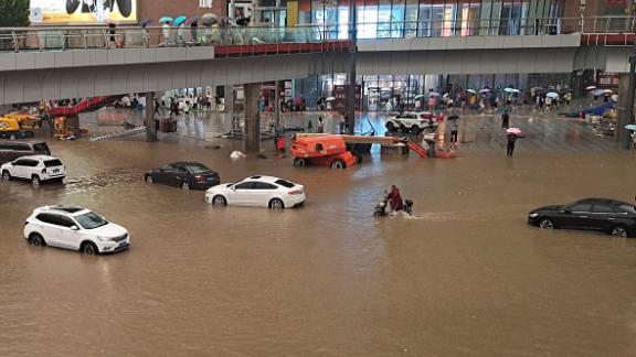 People stranded in flood waters along a street following heavy rains in Zhengzhou, China, on July 20.