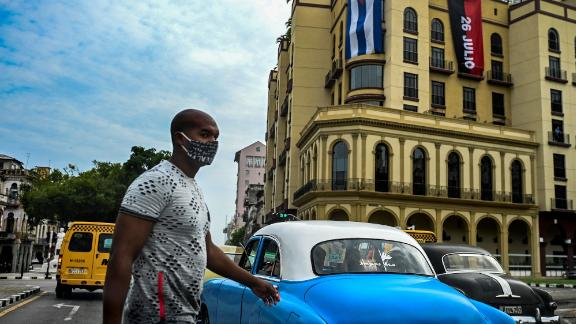 A man wearing a face mask crosses a street of Havana, on July 14, 2021. - One person has died in the anti-government protests across Cuba, according to officials, with activists saying at least 100 people have been arrested and scores remain in detention as demonstrations overseas in solidarity continued. (Photo by YAMIL LAGE / AFP) (Photo by YAMIL LAGE/AFP via Getty Images)