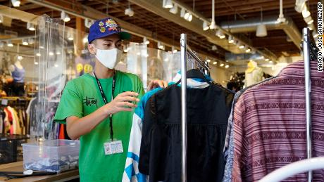 An employee sorts a clothes rack at the 2nd Street thrift store Monday in the Fairfax district of Los Angeles.
