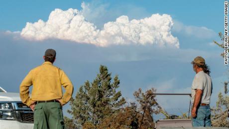 अग्नि शमन आणि शिक्षण तज्ञ रायन बर्लिन (एल) आणि बॉब डिलन 16 ऑगस्ट 2021 रोजी ओरेगॉन मधील बीटी येथे डिलनच्या घराबाहेर बुटले अग्नीच्या धुराचे ढग पाहतात.