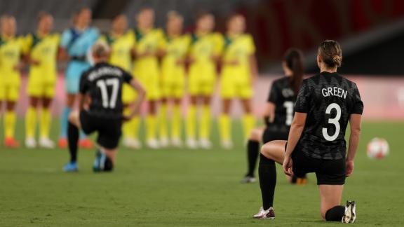 Anna Green in the New Zealand team's No. 3 jersey takes a knee along with her teammates before the game against Australia.