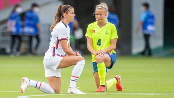 Alex Morgan of the US and Hanna Glas of Sweden take a knee before the start of their match.