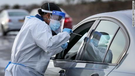 Nurse practitioner Deborah Beauplan administers a COVID-19 swab test at a drive-thru testing site set up for Suffolk County employees and their families at Smith Point Park in Shirley, New York on December 19, 2020.