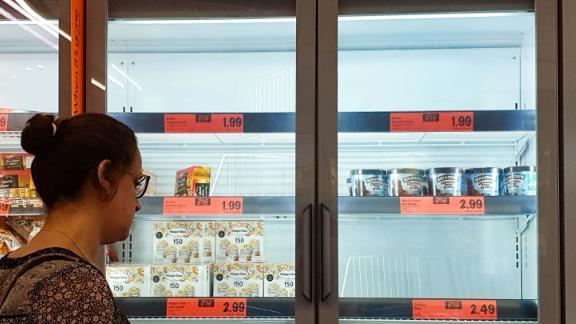 Un client regarde le stock de glaces épuisé dans un supermarché Lidl.