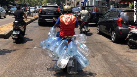 23. juni 2021 i Beirut kjører en mann på scooteren for å fylle opp med tomme vannflasker bensin.