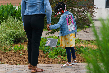 Saleemah Graham-Fleming holds her daughter's hand while looking at a memorial for Sanaa who was killed in April.