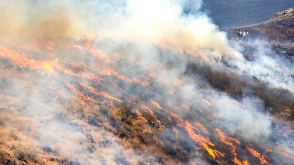 People stand behind the fire line as flames from the Steptoe Canyon Fire spread through dry grass in Colton, Washington, on Thursday, July 22.