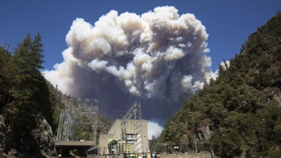 Plumes of smoke from the Dixie Fire rise above California's Plumas National Forest, near the Pacific Gas and Electric Rock Creek Power House, on Wednesday, July 21.