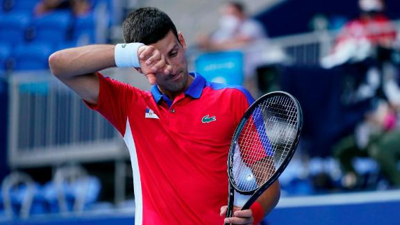 Novak Djokovic wipes sweat from his brow during his match against Bolivia's Hugo Dellien.