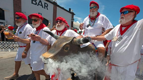 Ernest Hemingway look-alikes push a fake bull with smoke emanating from its nostrils during the
