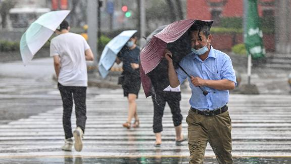 People cross the street in the wind and rain along in Ningbo on July 25, as Typhoon In-Fa lashes the eastern coast of China.