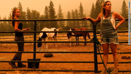 Residents wait for a trailer to evacuate horses at a ranch along State Route 89 during the Dixie Fire in Crescent Mills, California, on Saturday, July 24.