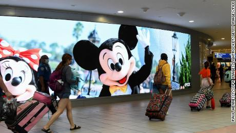 Travelers walk past a sign advertising Walt Disney World at Orlando International Airport as the July Fourth holiday weekend begins, on July 2, 2021.