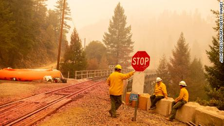 Employees of the Burlington Northern Santa Fe train lines protect train tracks with a mobile sprinkler system during the Dixie fire in Quincy, California, on July 26.