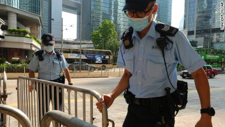 Police officers set up barriers ahead of Tong Ying-kit's arrival in court in Hong Kong on July 27.