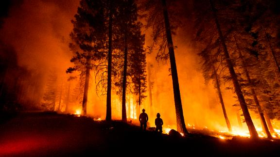 Cal Fire Capts. Tristan Gale, left, and Derek Leong monitor a firing operation in California's Lassen National Forest on Monday, July 26. Crews had set a ground fire to stop the Dixie Fire from spreading.