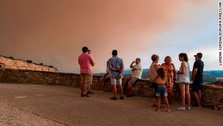 कैटेलोनिया के सेंट मार्टी डे टोस में फैली आग को स्थानीय लोग देखते हैं.