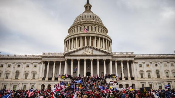 A large group of rioters stand on the East steps of the Capitol Building after storming its grounds on January 6, 2021 in Washington, DC.