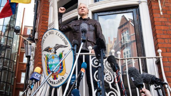 Julian Assange raises his fist as he steps out to speak to the media from the balcony of the Embassy Of Ecuador on May 19, 2017 in London.