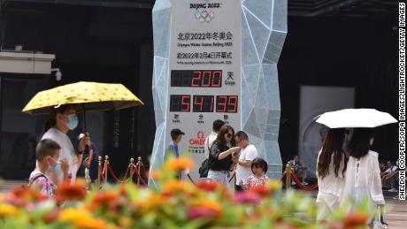 People wearing face masks walk past the countdown clock showing 200 days to the 2022 Olympic Winter Games.