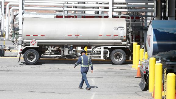 A worker walks by tanker trucks that are being filled with gasoline at an oil refinery in Utah.