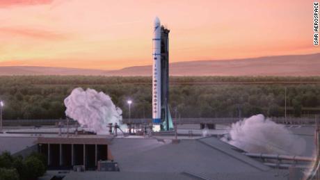 """Une interprétation d'artiste de la première génération d'Isar Aerospace """"Spectrum"""" fusée décollant d'une rampe de lancement imaginaire."""
