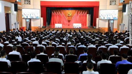 Members watch a live broadcast of the 100th anniversary of the founding of the Communist Party of China at the People's Assembly Hall in Rongan County, Liuzhou City on July 1, 2021.