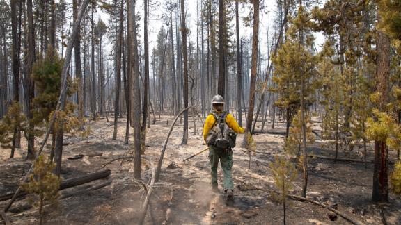 Firefighter Brentt Call walks through a burned over area of the Bootleg Fire near Klamath Falls, Oregon, on Tuesday, July 27.
