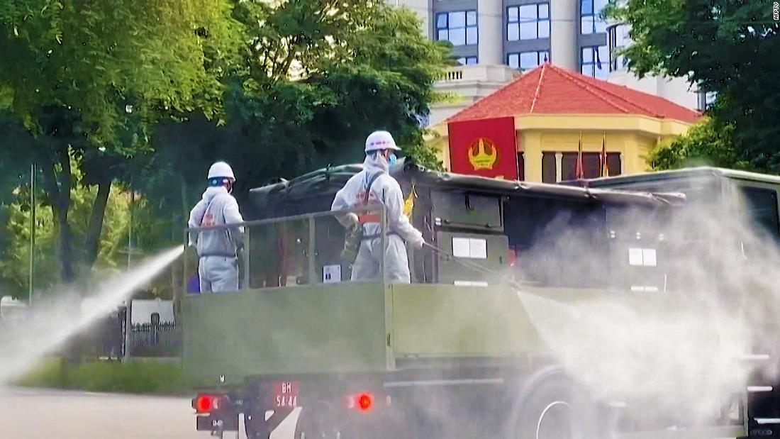 Soldiers in hazmat suits spray disinfectant as Vietnam sees rising cases
