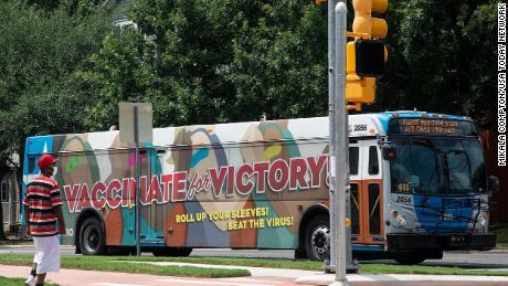 Een gemaskerde man loopt op 20 juli in Oost-Austin in een bus met een bericht waarin mensen worden opgeroepen zich te laten vaccineren tegen het coronavirus.