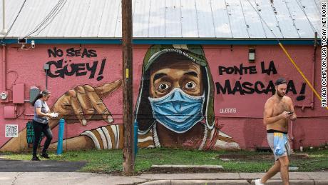 Mensen passeren een muurschildering waarin iedereen wordt opgeroepen maskers te dragen.  De muurschildering, gezien op dinsdag 20 juli in het Marcelino Restaurant in East Austin, is vertaald naar: