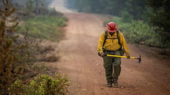 A firefighter from New Mexico walks up a dirt road after working to help contain the Bootleg Fire near Silver Lake, Oregon, on July 29, 2021.