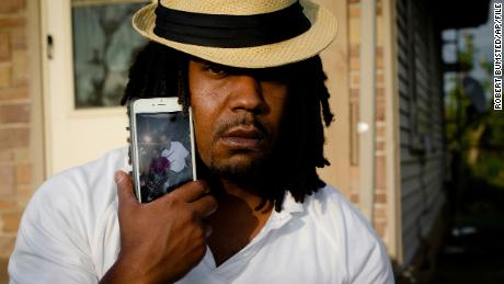 Dion Green holds a cell phone showing a picture of himself and his father, Derrick Fudge.