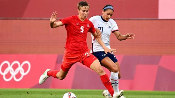 Tiền vệ người Canada Quinn (áo đỏ) là vận động viên bất nhị đầu tiên thi đấu tại Thế vận hội.