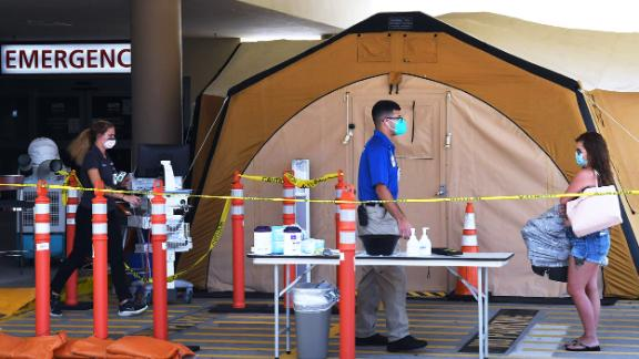A woman arrives at a treatment tent outside the emergency department at Palm Bay Hospital in Brevard County, Florida, on July 29, 2021.