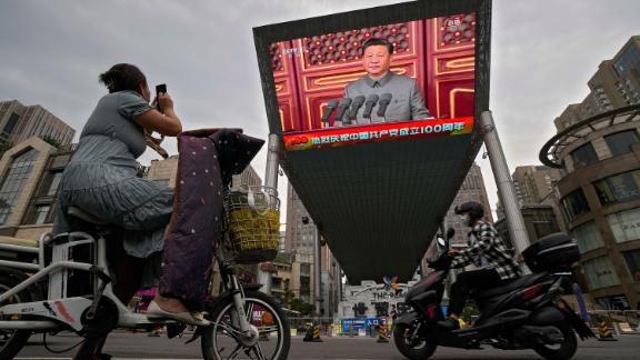 A woman on her electric-powered scooter films a large video screen outside a shopping mall showing Chinese President Xi Jinping speaking during an event to commemorate the 100th anniversary of China's Communist Party at Tiananmen Square in Beijing, Thursday, July 1, 2021.