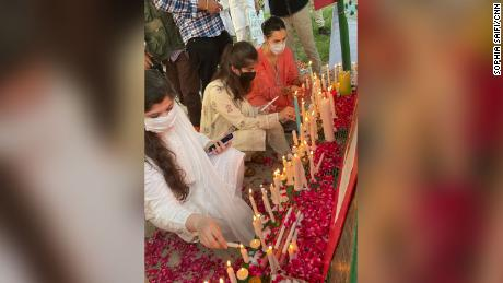 Women light candles at a vigil for Noor Mukadam in Islamabad.