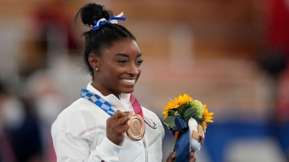 U.S. gymnast Simone Biles poses with her bronze medal for the artistic gymnastics women's balance beam apparatus at the 2020 Summer Olympics, Tuesday, Aug. 3, 2021, in Tokyo, Japan. (AP Photo/Natacha Pisarenko)