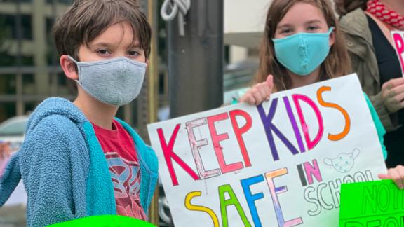 Will and Lila Hartley demonstrate for masks outside Tuesday's school board meeting.