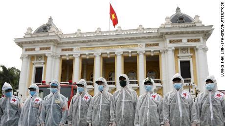 Soldados del Alto Comando Químico del Ministerio de Defensa Nacional de Vietnam antes de rociar desinfectante en las calles de Hanoi el 26 de julio.