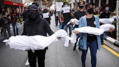 Los manifestantes llevan cuerpos falsos durante una manifestación cerca de la Plaza de la Independencia en Kuala Lumpur, para exigir la renuncia del primer ministro por su manejo de la pandemia de coronavirus.