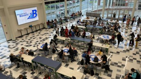 Students gather to catch up in the cafeteria on the first day of school, many not wearing masks.
