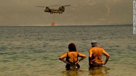 Les résidents locaux regardent un hélicoptère Chinook de l'armée grecque collecter de l'eau alors que les pompiers continuent de lutter contre un incendie de forêt près du village grec de Lambiri dimanche.