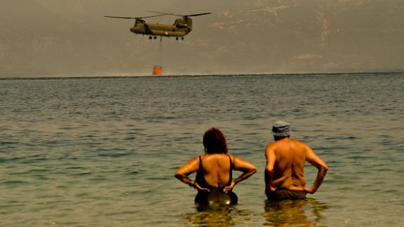 Local residents watch a Greek Army Chinook helicopter collect water as firefighters continue to fight a wildfire near the Greek village of Lambiri on Sunday.