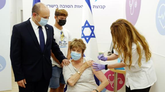 Prime Minister Naftali Bennett accompanies his mother for her booster shot in Haifa on Tuesday.