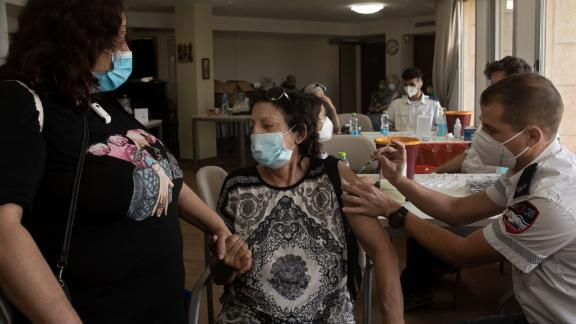 An Israeli woman receives a third coronavirus vaccine at a senior center in Jerusalem on Wednesday.