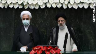 Raisi, right, takes his oath as president in Thursday's ceremony.